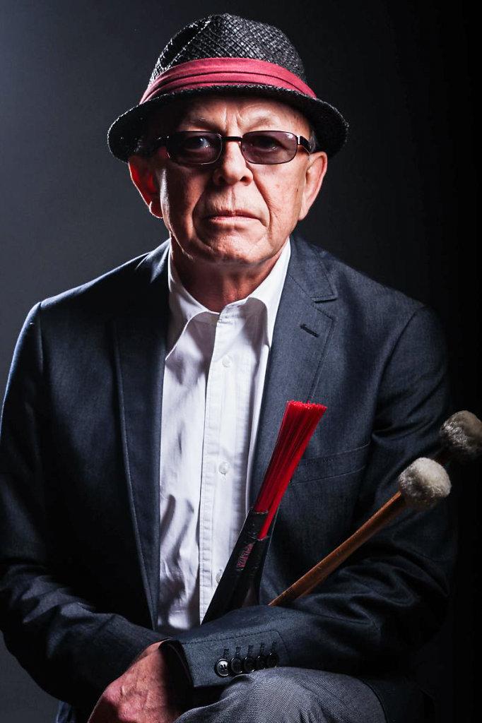 Musiker Janusz Maria Stefanski posiert vor  Kamera, er  ist fotografiert  mit Studio Blitz. er sitz am einen Stuhl.
